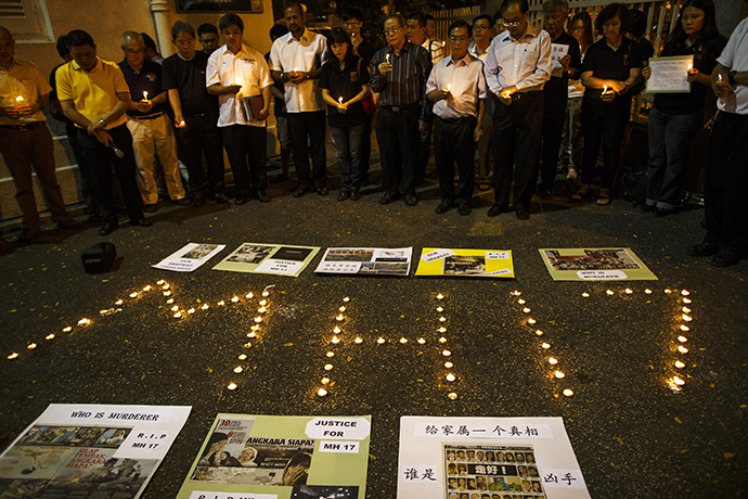 People hold candles during a candlelight vigil for victims of the downed Malaysia Airlines Flight MH17, in Kuala Lumpur July 19, 2014. (Reuters / Athit Perawongmetha)