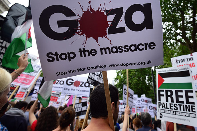 Protesters display placards and banners as they take part in demonstration against Israeli airstrikes in Gaza in central London on July 19, 2014 against Gaza strikes. (AFP Photo / Carl Court)
