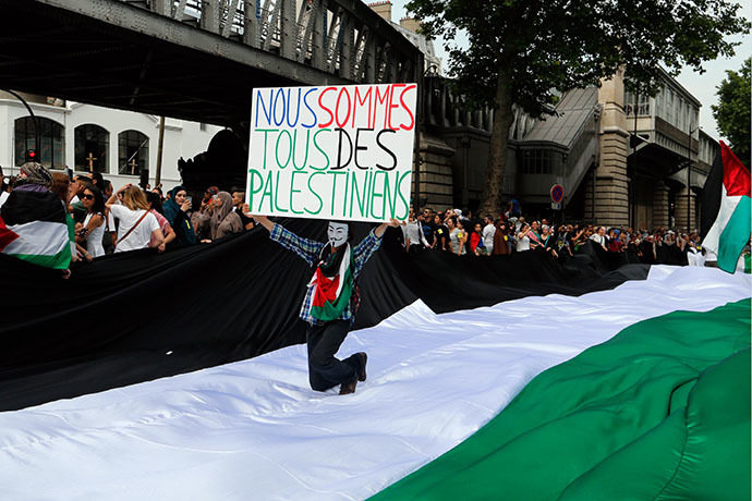 "A protester holds a placard reading ""We are all Palestinians"" as he kneels on a giant Palestinian flag near the Barbes-Rochechouart aerial metro station prior to the departure of a demonstration, banned by French police, in Paris on July 19, 2014 to denounce Israel's military campaign in Gaza and show support for the Palestinian people. (AFP Photo / Francois Guillot)"