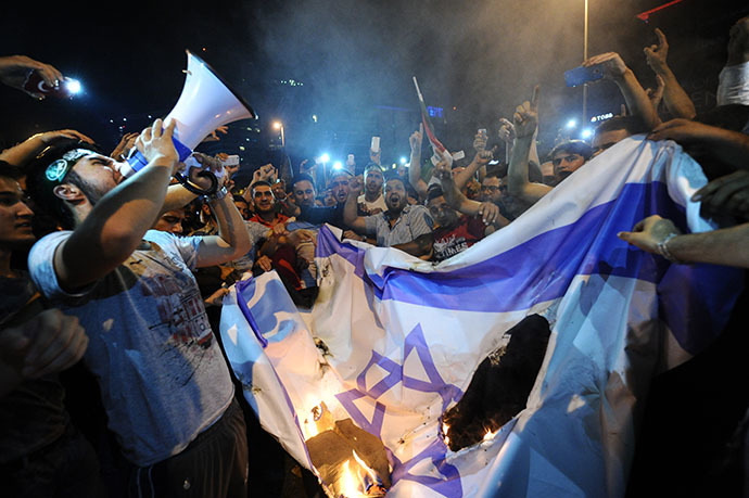 Turkish protestors set fire to Israel flag while they are shout slogans during a demonstration to denounce the Israeli military operations in Gaza on July 19, 2014 in front of the Israeli Consulate in Istanbul. (AFP Photo / Ozan Kose)