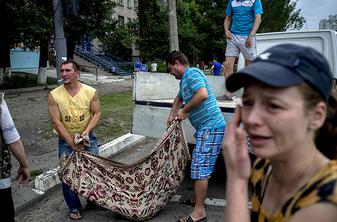 People in Lugansk carry the bodies of those killed during an artillery attack on the city on July 18, 2014. (RIA Novosti / Valeriy Melnikov)