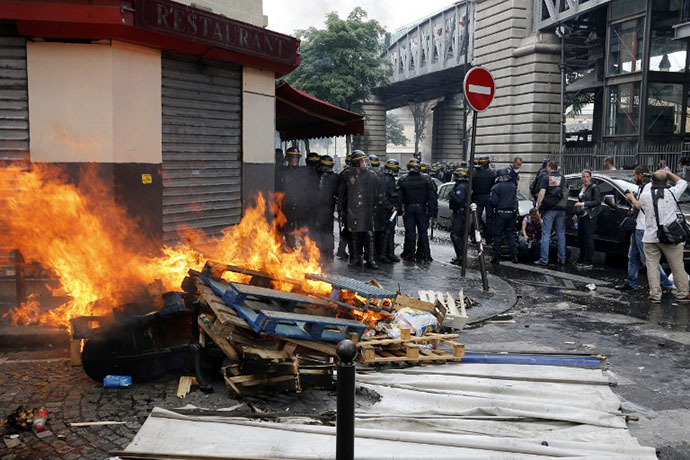 French riot police officers stand by burning pallets near the aerial metro station of Barbes-Rochechouart, in Paris, on July 19, 2014. (AFP Photo / Francois Guillot)