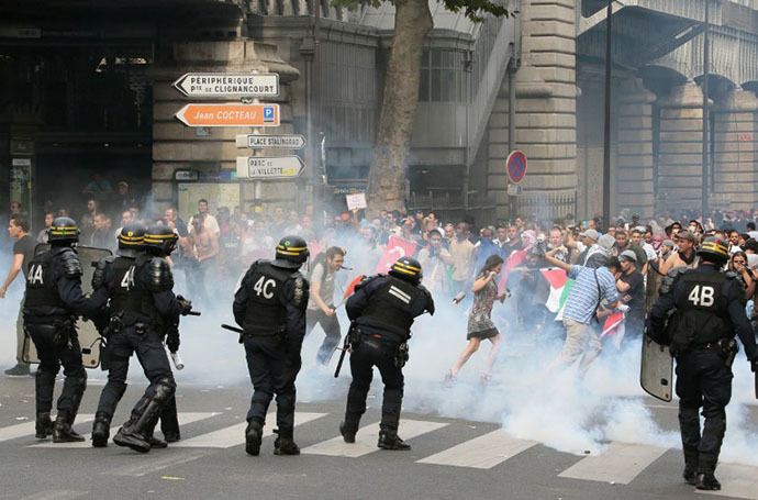 Protesters run away from tear gas as they clash with riot police near the Barbes-Rochechouart aerial metro station in Paris on July 19, 2014. (AFP Photo / Jacques Demarthon)