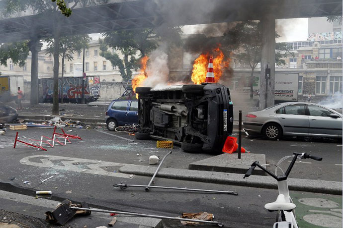 Burned vehicles owned by Paris public services are seen by the aerial metro station of Barbes-Rochechouart, in Paris, on July 19, 2014. (AFP Photo / Francois Guillot)