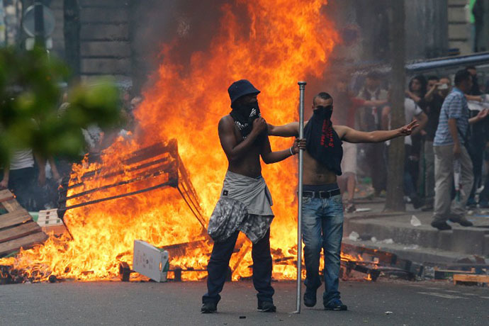 Protesters stand in front of a fire barricade near the aerial metro station of Barbes-Rochechouart, in Paris, on July 19, 2014. (AFP Photo / Francois Guillot)
