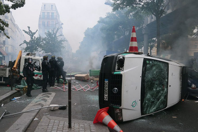 Riot police stand next to an overturned Paris public transport operator RATP van during clashes with protesters near the Barbes-Rochechouart aerial metro station in Paris on July 19, 2014. (AFP Photo / Jacques Demarthon)