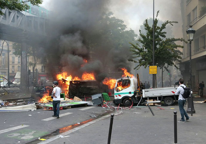 Protesters stand next to burning Paris public transport operator RATP trucks during clashes near the Barbes-Rochechouart aerial metro station in Paris on July 19, 2014. (AFP Photo / Jacques Demarthon)