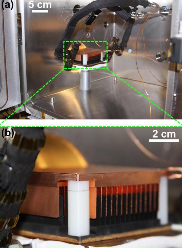 "(a) Image of the experimental setup inside the chamber with a (b) magnified view of the cold-plate showing the interdigitated CuO and Cu combs sitting on top. (Screenshot from the article ""Jumping-Droplet Electrostatic Energy Harvesting"" by Nenad Miljkovic, Daniel J. Preston, Ryan Enright and Evelyn N. Wang, published in Applied Physics Letters, July 2014)"