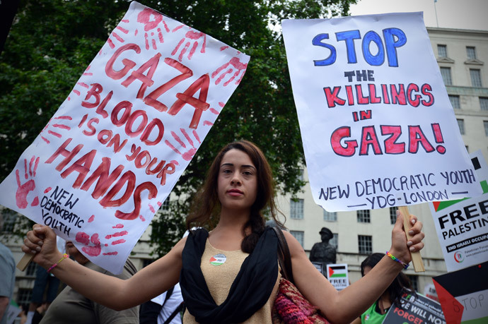 A protestor displays banners as she takes part in demonstration against Israeli airstrikes in Gaza in central London on July 19, 2014 against Gaza strikes. (AFP Photo / Carl Court)