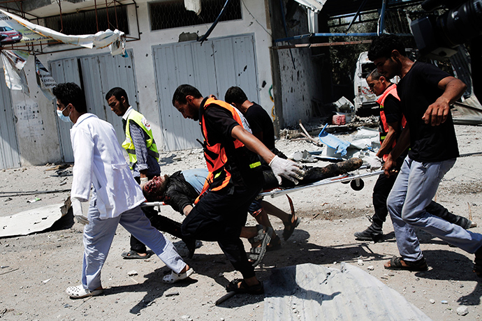 Medics carry a wounded Palestinian man through the Shejaia neighbourhood, which was heavily shelled by Israel during fighting, in Gaza City July 20, 2014 (Reuters / Finbarr O'Reilly)