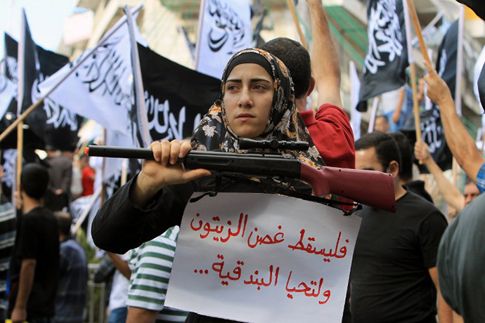 A Palestinian protester holds a placard and a fake weapon during a demonstration to support the resistance in Gaza and to protest against the Israeli military offensive on the Palestinian Gaza Strip on July 20, 2014 in the West Bank city of Ramallah. (AFP Photo / Abbas Momani)