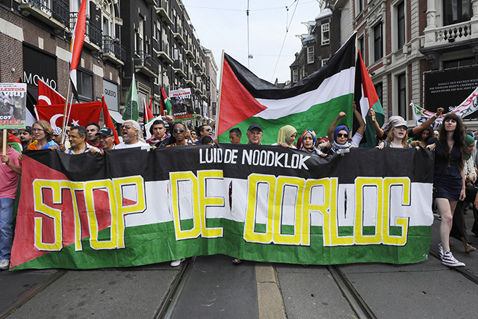 "Protesters carry a banner depicting the Palestinian flag reading ""Sound the alarm, Stop the War"" as they take part in a demonstration in Amsterdam on July 20, 2014, to protest Israel's military campaign in Gaza and show their support for the Palestinian people. (AFP Photo / John Thys)"