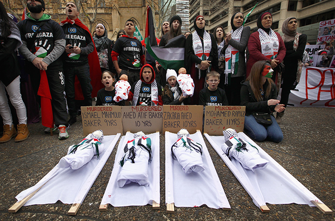Children sit in front of dolls on stretchers as they and other members of the Australian Palestinian community hold a protest against Israel's military action in Gaza, in Sydney July 20, 2014. (Reuters / David Gray)