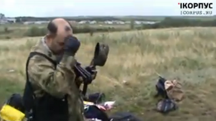 A member of Donetsk self-defense forces takes off his cap and crosses himself to pay tribute to the victims of the Malaysia plane crash (screenshot from infrocorpus)