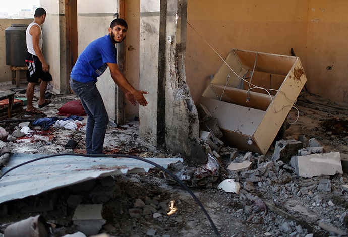 Palestinians inspect a damaged house which police said was hit by an Israeli shelling that killed 8 members from al-Qassas family, among them four children, in Gaza City July 21, 2014 (Reuters / Suhaib Salem)