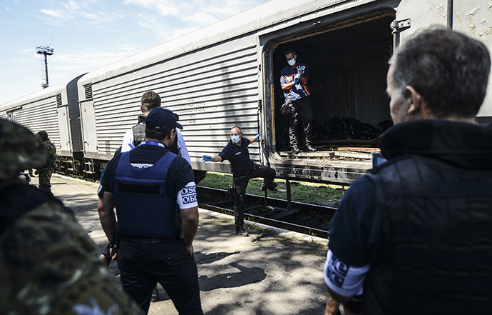 Monitors from the Organization for Security and Cooperation in Europe (OSCE) and members of a forensic team inspect a refrigerator wagon containing the remains of victims from the downed Malaysia Airlines Flight MH17, at a railway station in the eastern Ukrainian town of Torez on July 21, 2014. (AFP Photo / Bulent Kilic)