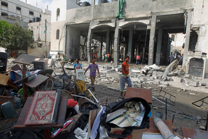Palestinian boys walk past debris, including Korans and other items from a mosque destroyed in an overnight Israeli military strike, on July 22, 2014, in Rafah the southern Gaza Strip. (AFP Photo / Said Khatib)