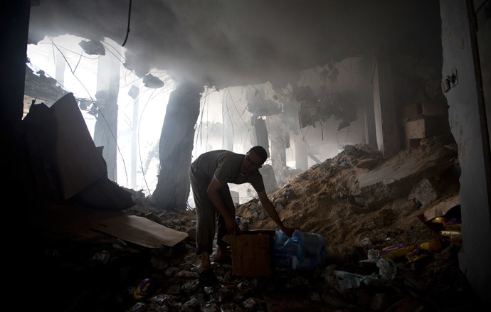 A Palestinian man removes goods from the rubble of a destroyed store located on the ground floor of a building hit by an Israeli air strike on July 22, 2014 in Gaza city. (AFP Photo / Mahmud Hams)