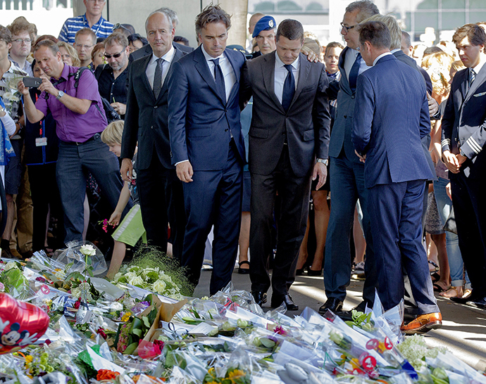 Deputy general director of Air France-KLM airline company Camiel Eurlings (2-L) and Chief Operating officer at KLM Pieter Elbers (3-R) stand in front of flowers laid for the victims of the downed Malaysia Airlines flight MH17 at the Schiphol Airport near Amsterdam, on July 23, 2014. (AFP Photo / Sander Koning)