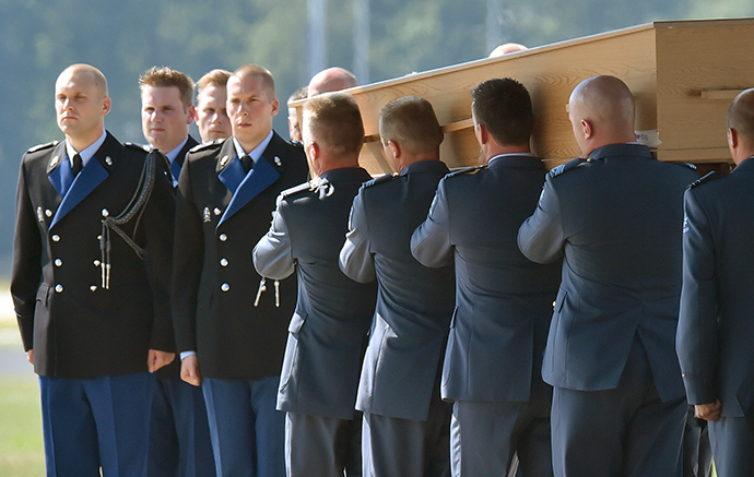 Military men carry a coffin containing the remains of a victim of downed Malaysia Airlines flight MH17, during a ceremony at Eindhoven Airbase on July 23, 2014. (AFP Photo / John Thys)