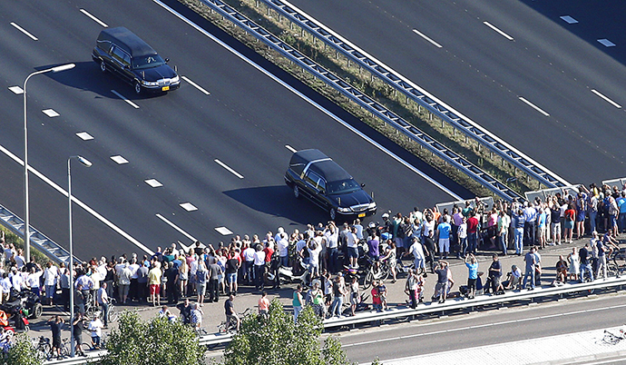 This aerial photo shows people watching from a bridge a convoy of hearses carrying coffins containing the remains of victims of the downed Malaysia Airlines flight MH17, driving from the Eindhoven Airbase to Hilversum on July 23, 2014. (AFP Photo / Jerry Lampen)