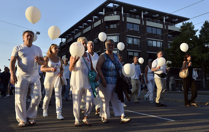 People wearing white clothes hold balloons during a silent march in memory of the victims of the downed Malaysia Airlines flight MH17, on July 23, 2014 in Amsterdam. (AFP Photo / John Thys)