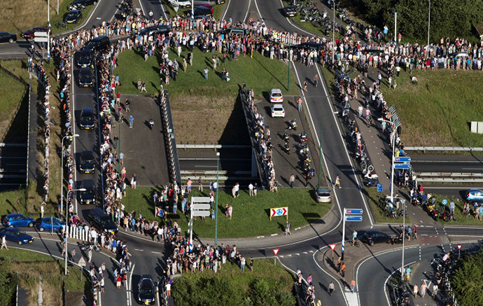 An aerial view taken on July 23, 2014 shows people standing on the side of the road as the convoy of hearses carrying the bodies of victims of the downed Malaysia Airlines flight MH17 is on its way to Hilversum where the bodies will be examined. (AFP Photo / Jerry Lampen)
