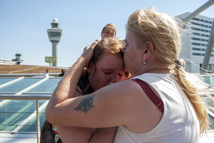People embrace while paying their respects at Schiphol Airport during a national day of mourning for the victims of the downed Malaysia Airlines flight MH17, in Schiphol July 23, 2014. (Reuters / Cris Toala Olivares)