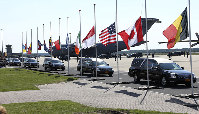 The convoy of hearses with the remains of the victims of Malaysia Airlines MH17 downed over rebel-held territory in eastern Ukraine, drives past international flags as it leaves Eindhoven airport to a military base in Hilversum July 23, 2014. (Reuters / Francois Lenoir)