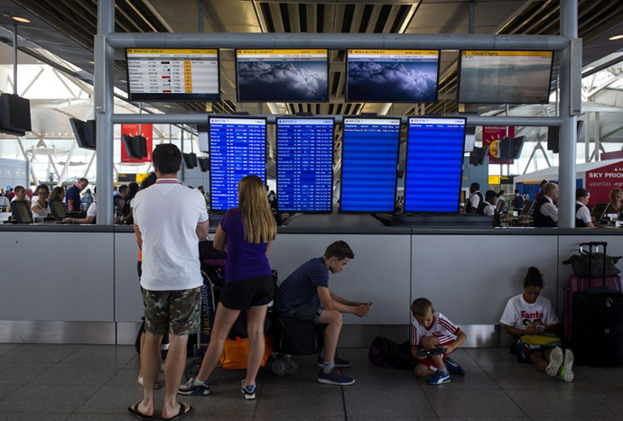 People stand in the Delta Airlines terminal at John F. Kennedy Airport July 22, 2014 in New York City. (AFP Photo / Getty Images / Eric Thayer)