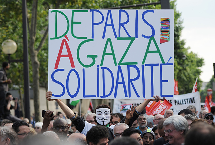 "A man holds a placard reading ""From Paris to Gaza, Solidarity"", as protesters take part in a demonstration on July 23, 2014 in front of the Invalides in Paris, to denounce Israel's military campaign in Gaza and to show their support to the Palestinian people (AFP Photo / Stephane De Sakutin)"