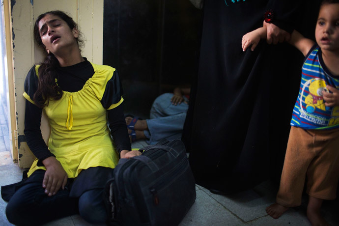 A Palestinian girl who fled what medics said was Israeli shelling that hit a U.N-run school sheltering Palestinian refugees, sits in shock at a hospital in Beit Hanoun in the northern Gaza Strip July 24, 2014.(Reuters / Finbarr O'Reilly)