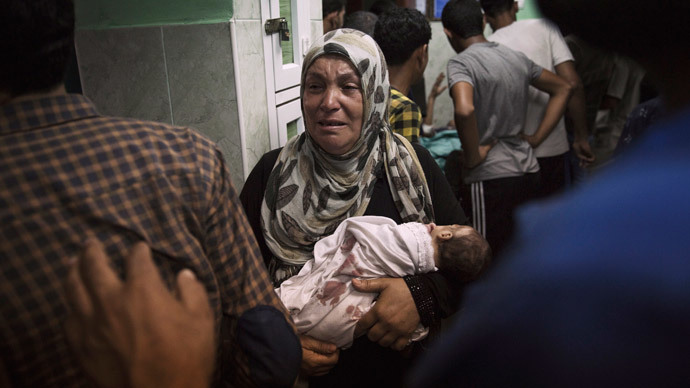 A Palestinian woman holds an infant, whom medics said was injured in an Israeli shelling at a U.N-run school sheltering Palestinian refugees, at a hospital in the northern Gaza Strip July 24, 2014.(Reuters / Finbarr O'Reilly)
