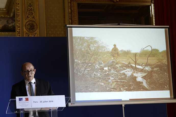 French Defence minister Jean-Yves Le Drian delivers a press conference at the Quai d'Orsay on June 25, 2014 with behind him an image released by ECPAD showing French soldiers standing by the wreckage of the Air Algerie flight AH5017 which crashed in Mali's Gossi region, west of Gao, the day before. (AFP Photo / Stephane de Sakutin)