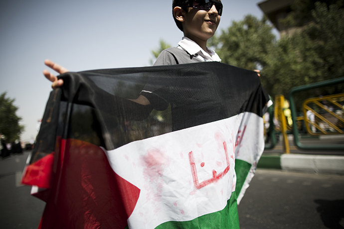 An Iranian boy holds a Palestinian flag during a demonstration in Tehran on July 25, 2014 to mark Quds (Jerusalem) Day. (AFP Photo / Behrouz Mehri)