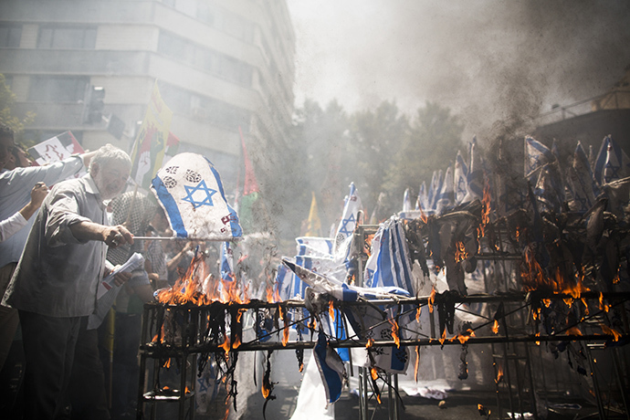 Iranian protestors burn Israeli flags during a demonstration in Tehran on July 25, 2014 to mark the Quds (Jerusalem) Day. (AFP Photo / Behrouz Mehri)