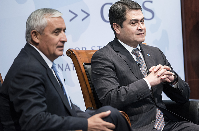 President of Guatemala Otto Perez Molina (L) and President of Honduras Juan Orlando Hernandez wait to speak during an event at the Center for Strategic and International Studies July 24, 2014 in Washington, DC. (AFP Photo / Brendan Smialowski)
