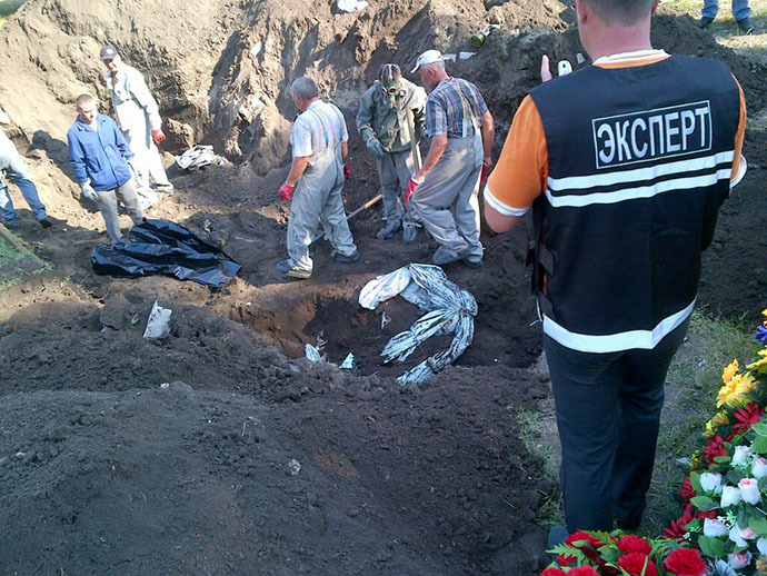 Experts dig a hole to exhume four unidentified bodies at a mass grave in the eastern Ukrainian city of Slavyansk on July 24, 2014. (AFP Photo / Marion Thibaut)