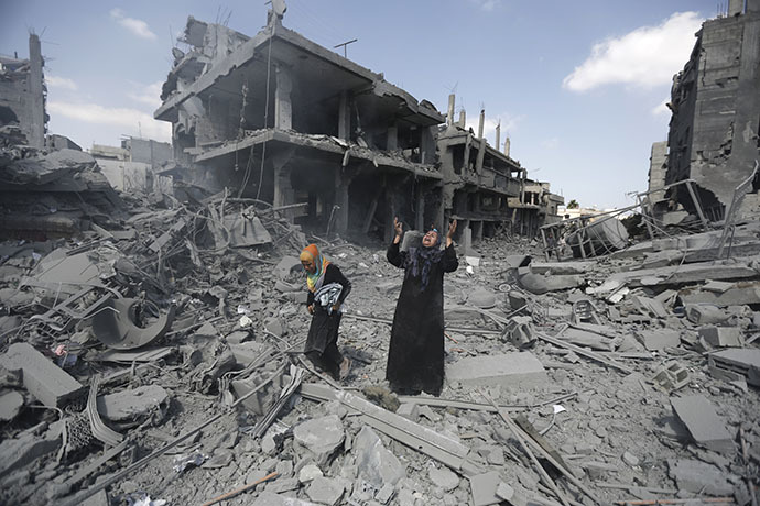 A Palestinian woman pauses amid destroyed buildings in the northern district of Beit Hanun in the Gaza Strip during an humanitarian truce on July 26, 2014. (AFP Photo / Mohammed Abed)