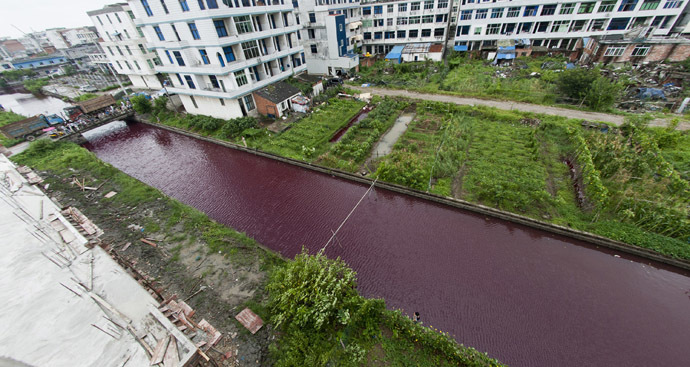 This picture taken on July 24, 2014 shows a river with its water turned to red in Wenzhou, east China's Zhejiang province. (AFP Photo/China Out)