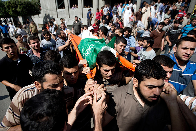 Palestinian mourners carry the body of Mahmud Abu al-Hosna, whose body was retreived from the rubble the day before, during his funeral in Jabalia in the northern Gaza Strip on July 27, 2014. (AFP Photo / Mahmud Hams)
