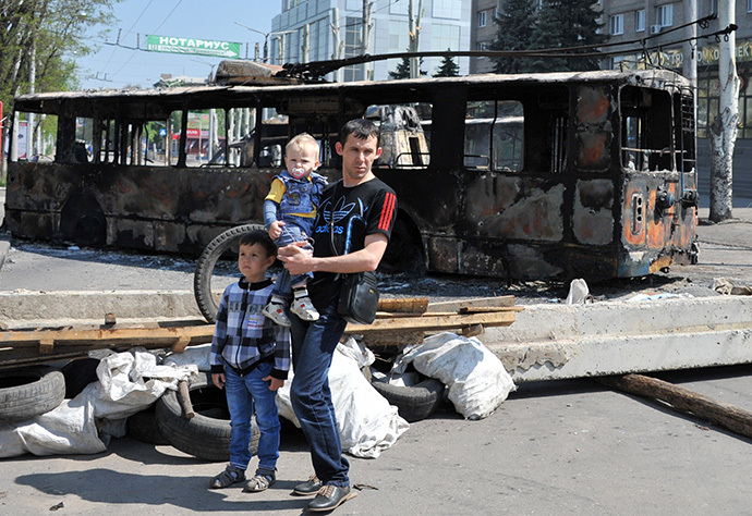 A man with his children stands near a trolleybus which was burned overnight during fightings between anti-government militias and Ukranian troops in the eastern Ukranian city of Kramatorsk. (AFP Photo / Genya Savilov)