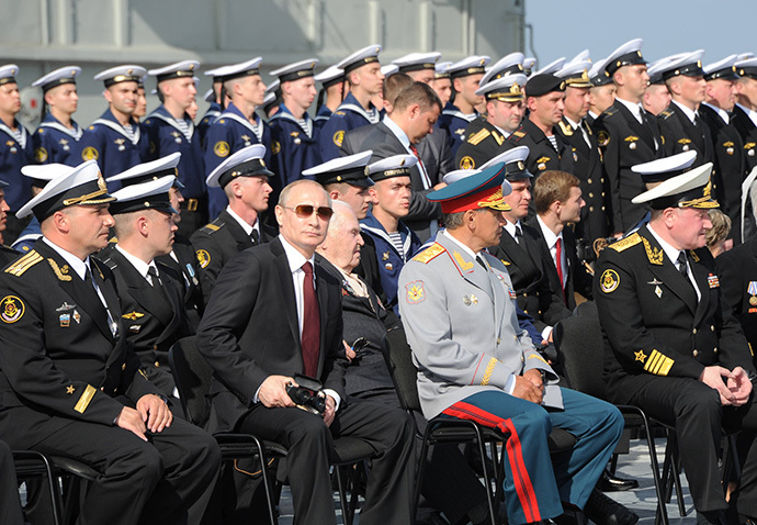 Russian President Vladimir Putin, 1st row 3rd left, is seen on board the Admiral Kuznetsov aircraft carrier watching a parade and a staged performance by combat ships of Russia's Northern Fleet, July 27, 2014. (RIA Novosti / Michael Klimentyev)