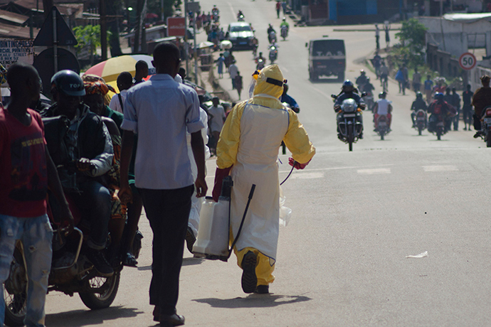 A health worker with disinfectant spray walks down a street outside the government hospital in Kenema, July 10, 2014 (Reuters / Tommy Trenchard)