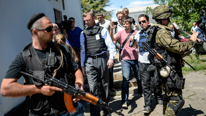 Chief of Monitors from the Organization for Security and Cooperation in Europe (OSCE) Alexander Hug walks with separatists at a railway station in the eastern Ukrainian town of Torez.(AFP Photo / Bulent Kilic)