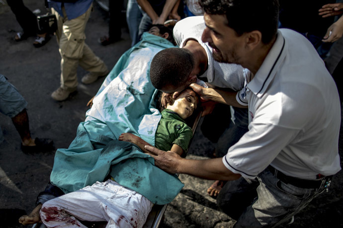 A Palestinian man mourns over the bodies of two children, killed in an explosion in a public playground on the beachfront of Shati refugee camp, as they are wheeled into al-Shifa hospital in Gaza City on July 28, 2014. (AFP Photo/Marco Longari)