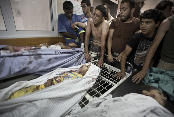 Palestinian mourners and medics gather over the bodies of six of the eight children who were killed in an explosion in a public playground in the beachfront Shati refugee camp in Gaza City on July 28, 2014. (AFP Photo/Mahmud Hams)