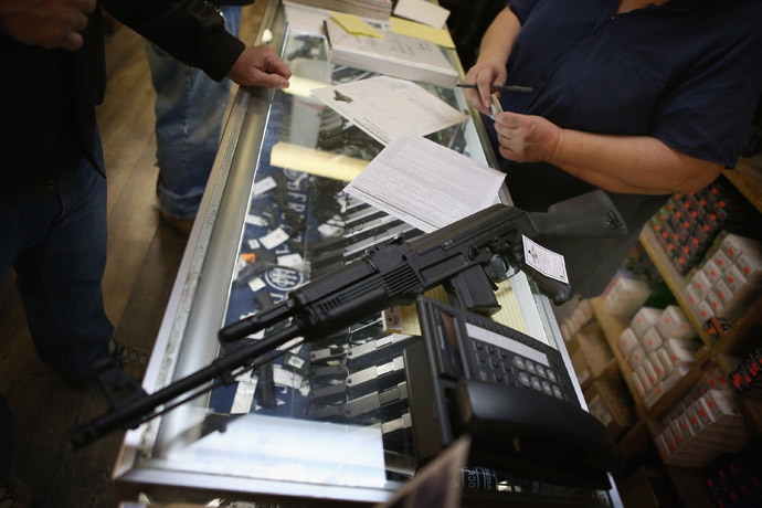 A customer purchases an AK-47 style rifle for about $1200 at Freddie Bear Sports sporting goods store in Tinley Park, Illinois. (Scott Olson / Getty Images / AFP)