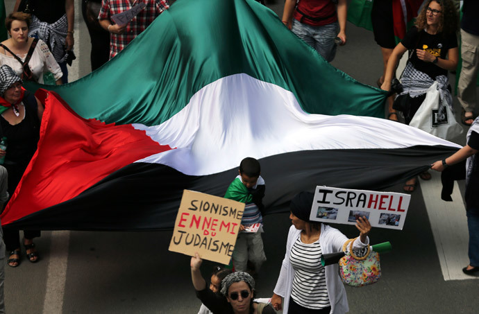 Demonstrators hold a giant Palestinian flag and anti-Israel signs during a protest against the Israeli offensive on the Gaza Strip, in central Brussels July 27, 2014.(Reuters / Francois Lenoir)