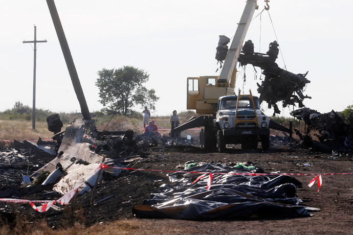 A crane moves wreckage at the crash site of Malaysia Airlines Flight MH17 in front of body bags near the village of Hrabove, Donetsk region, July 20, 2014.(Reuters / Maxim Zmeyev )
